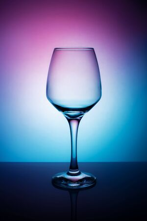 Wine glass on a purple white blue background. Still life with a beautiful light.
