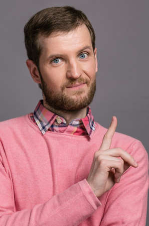 attract: Man in a pink sweater raised his index finger up. gesture to attract attention Stock Photo