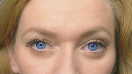 Beautiful blue eyes close-up. A young woman is blinking and is looking at the camera. close-up,