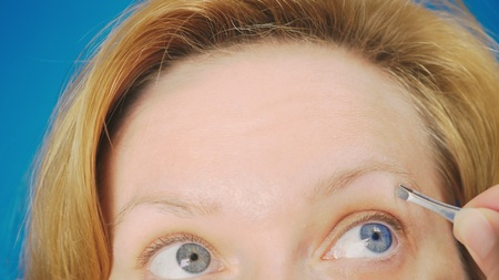 Extreme close-up. plucking eyebrows tweezers, a blonde girl with blue eyes pulls out unnecessary hairs from her eyebrow