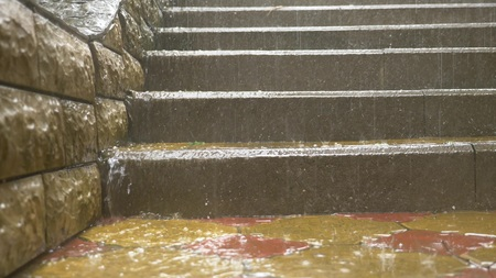 streams of water pour down the steps of the stairs in the park during a pouring rain.