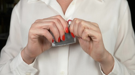 close-up. women's hands try to open the condom package. The concept of safe sex and contraception 스톡 콘텐츠