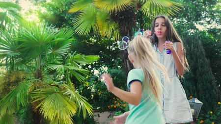 two girls, brunette and blond blowing soap bubbles against a tropical park background. Foto de archivo