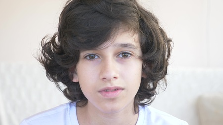 cute curly-haired boy teen looking into camera