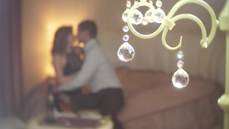 Focus on the round crystals from the lamp. Ardent loving couple is sitting on bed and hugging with passion on background. Romantic date concept. blur.