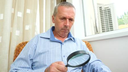 A man a pensioner reads a book through a magnifying glass at home by the window.