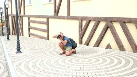 male photographer is taking pictures in the street with the help of a professional camera. copy space