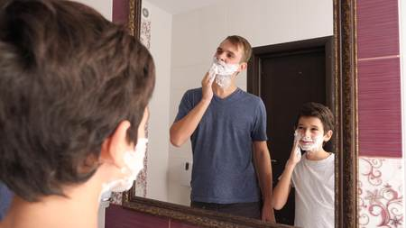 Father and son in the bathroom in the morning, little boy copies his father shaving. Stock Photo