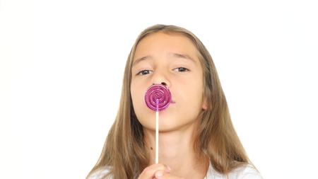 A little girl licks a lollipop stares into the camera and makes funny faces. copy space