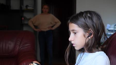mom scolds her daughter in her room, and she ignores her and listens to music on headphones. copy space Banco de Imagens