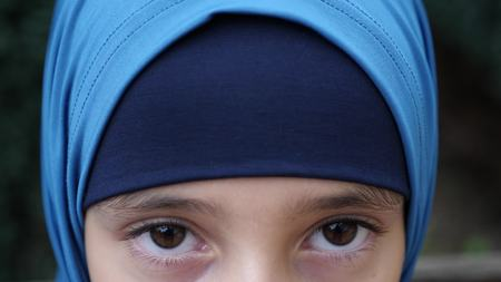 portrait of a modest girl, a Muslim wearing a hijab looks at the camera. copy space Stock Photo