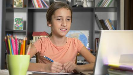 concept of online learning. the child is enrolled in an online school. girl doing homework with laptop.