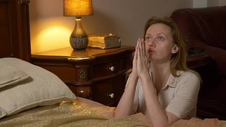 a young blonde woman praying before going to bed. Reklamní fotografie