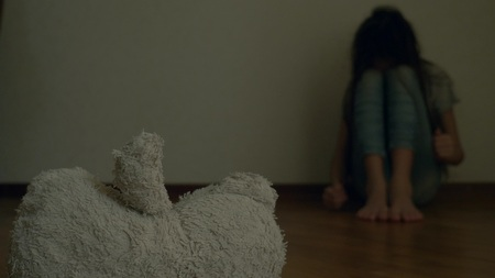 a desperate child in depression sits at the wall of his room, tries to attempt suicide. next to it is an abandoned soft toy Foto de archivo - 110379016