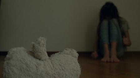 ein verzweifeltes Kind in Depressionen sitzt an der Wand seines Zimmers und versucht einen Selbstmordversuch. daneben ist ein verlassenes Stofftier