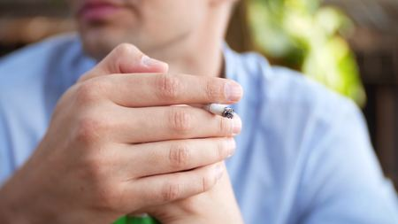 Young man and smoking cigarette in the bar outdoors. background blur.