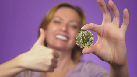 a young woman with a white-toothed smile in the background is blurry, holds in her hand a bitcoin gold coin. bitcoin sharpness. color background