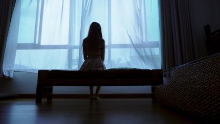 kleine tiener kijkt uit het raam bij slecht weer, silhouet van een kwetsbaar tienermeisje op de achtergrond van een groot raam Stockfoto
