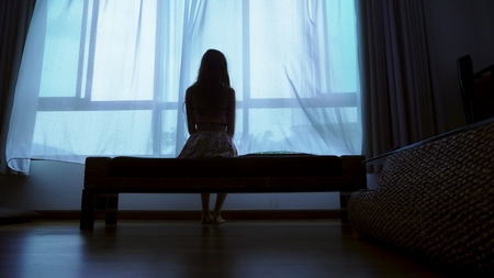 little teenager looking out of the window in bad weather, silhouette of a fragile teenager girl on the background of a large window