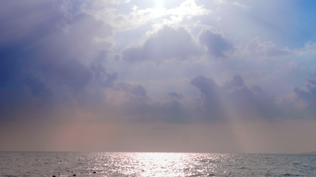 the suns rays shine through beautiful white clouds above the sea.