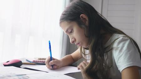 Teenage girl doing homework for school in her room, on the desk 스톡 콘텐츠