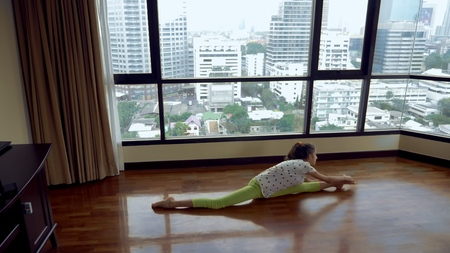 slim young girl stretching in front of a large panoramic window overlooking the skyscrapers