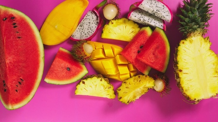 tropical fruit on a bright pink background. slices Minimal fruit concept.