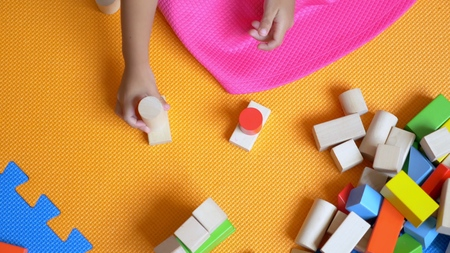 Little Asian cute girl playing cubes, sitting on a color floor. The concept of child development.