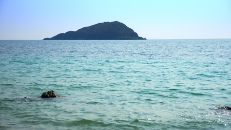view from the shore to a tropical island in the sea