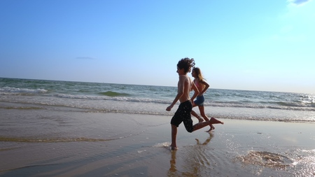 Happy teenagers run along the seashore. catch-up game on the beach Stockfoto