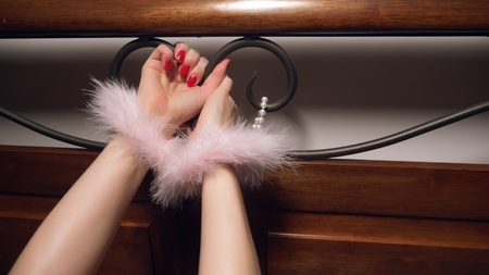 the hands of a woman in fur handcuffs are held by a wrought headboard. close-up