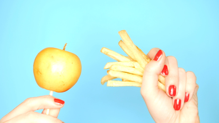 Concept of healthy and unhealthy food. An apple against french fries on a bright blue background. female hands with red nail polish hold apple and french fries