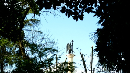 blurred silhouette statue of an angel with a sword against the blue sky in the frame of foliage