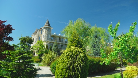 luxurious hotel in Victorian style, immersed in beautiful trees and bushes. roofs with spiers on a background of clear blue sky