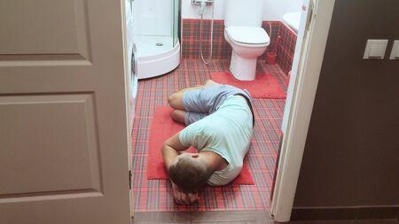 El hombre estaba tendido en el piso del baño, al lado del inodoro luego de una sobredosis de alcohol o drogas.