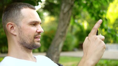 close-up. A man blogger uses a smartphone while sitting on a park bench. He has a video call with someone