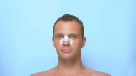 Concept of plastic surgery, a man after a plastic surgery on the face, rhinoplasty, with a bandage on the nose. on blue background. Stock Photo