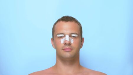 The concept of plastic surgery, a man after a plastic surgery on the face, rhinoplasty and blepharoplasty, with a bandage on the nose and eyelids. on blue background.