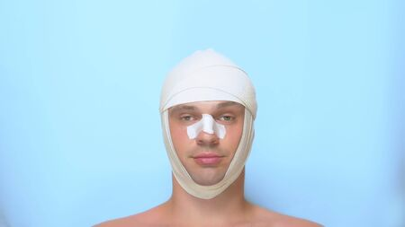 a man after a plastic surgery facelift, rhinoplasty, blepharoplasty. with a bandage on the nose, head and eyes. on blue background. shows a super sign and okay