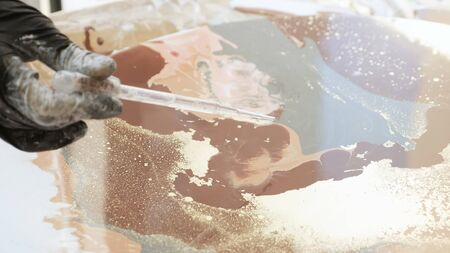 Process of Fluid art acrylic painting. Pouring acrylic paint at circle canvas . Close-up, someone drops alcohol from a pipette onto fresh acrylic paints. the process of interaction of acrylic paints a