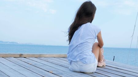 Teen girl sits alone on a wooden bridge at the sea and looks sad at the sea 免版税图像