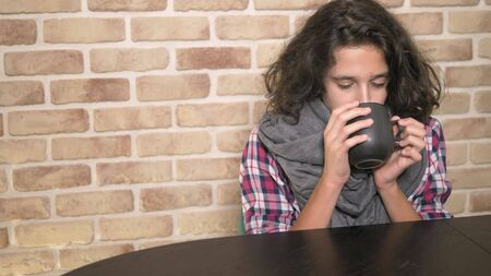 The concept of seasonal fever. Sick teenager boy holding a cup of hot drink. Unhappy teenager with curly brunette hair, in a plaid shirt and a gray scarf sits at a table against a brick wall 스톡 콘텐츠