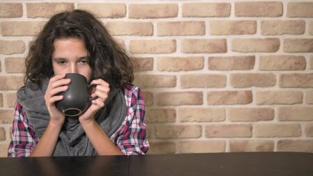 The concept of seasonal fever. Sick teenager boy holding a cup of hot drink. Unhappy teenager with curly brunette hair, in a plaid shirt and a gray scarf sits at a table against a brick wall 스톡 콘텐츠 - 129064822