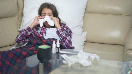 une adolescente enrhumée se mouche allongée sur le canapé sous les couvertures.