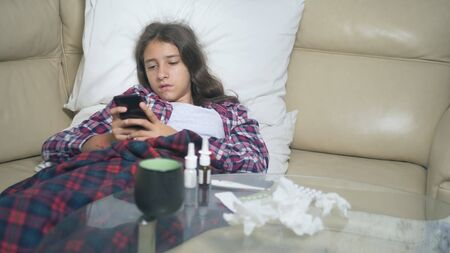 sick girl holding a smartphone. cold teen girl covers with winter flu blanket resting at home.