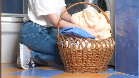 close-up. woman takes laundry out of the dryer and puts it in a wicker basket Archivio Fotografico
