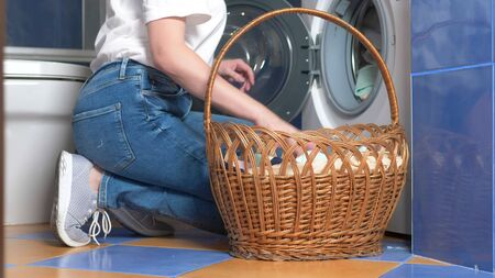 close-up. unrecognizable woman putting cloth in washing machine from laundry basket Stok Fotoğraf