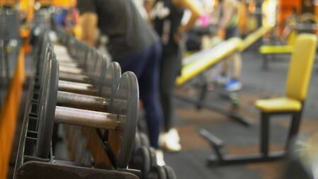 Blur background. dumbbells in the gym. people doing exercises with dumbbells in the gym