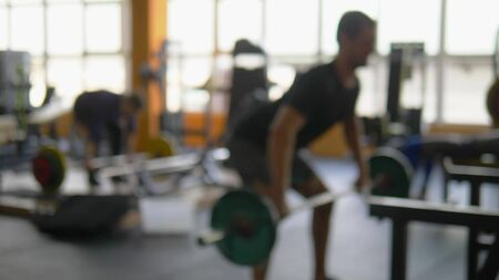 Blur background. barbells in the gym. Blurred fitness room with weight training bar