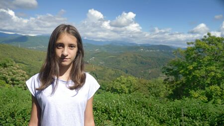 portrait. charming teen girl on a background of magnificent mountain landscape and blue sky 版權商用圖片